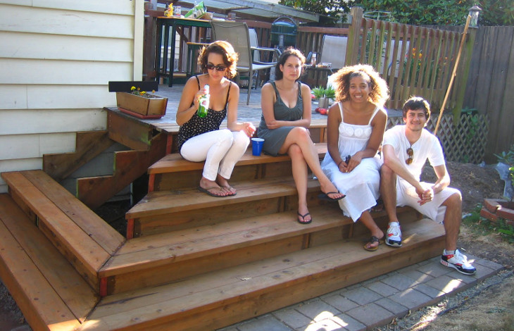 Friends sitting on deck stairs