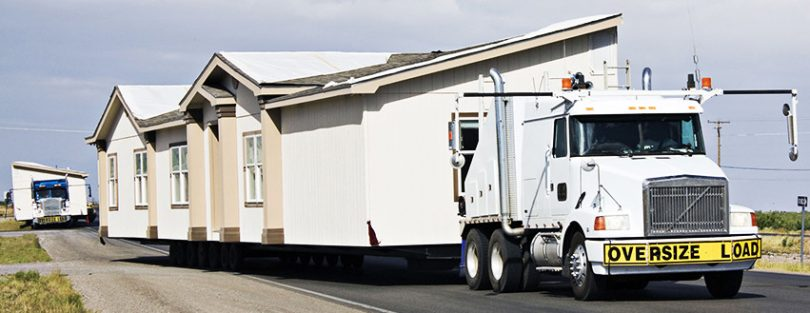 Trucks moving mobile homes
