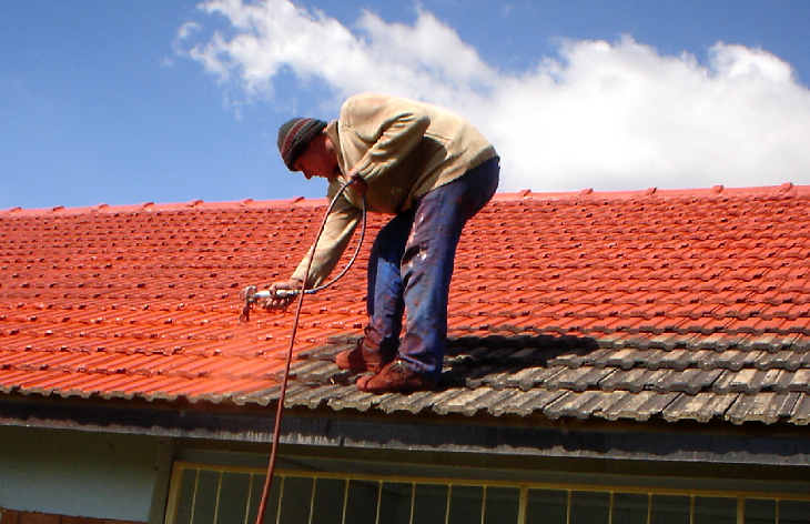 Spraying sealant on roof